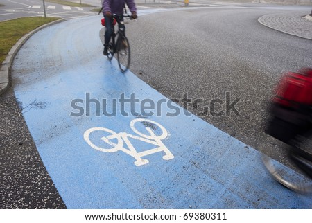 Two busy cyclist passing by on their way to job in the winter morning - Denmark. Motion blur. - stock photo