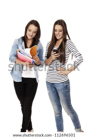 two busy students one with notepads one with smartphone on white background - stock photo