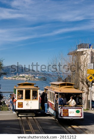 Two cablecars on top of a San Francisco Hill, with Alcatraz in the background. - stock photo