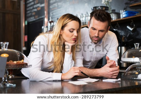 Two cafe managers counting revenue - stock photo