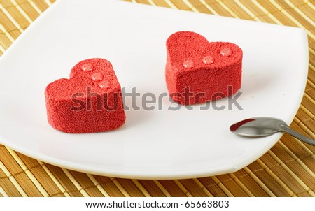 Two cakes representing hearts lay on a white plate. The teaspoon lays on a plate.