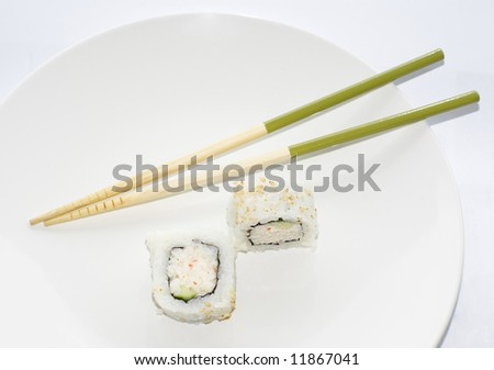Two California maki sushi rolls with green chopsticks ona white plate - stock photo