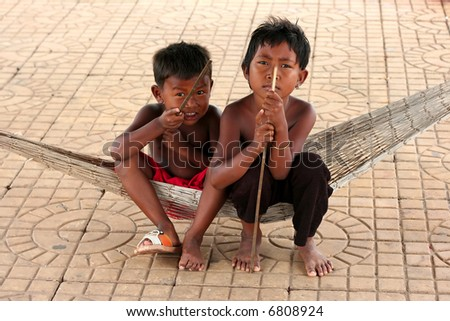 Two cambodian children sitting in a hammock - stock photo