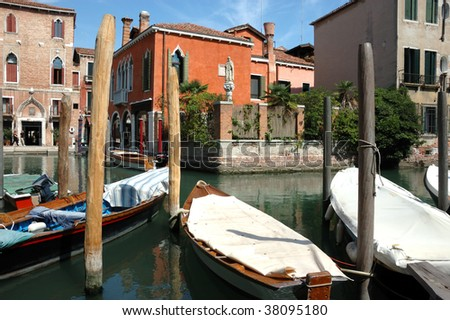 two canals meet in Venice, overlooked by an ancient statue. boats are parked around the crossing and beautiful venetian houses line the waterways - stock photo
