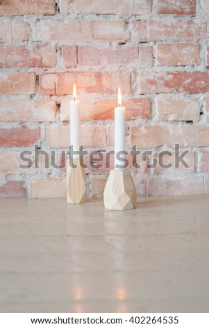 Two candlelights on table, with brick wall in the background - stock photo