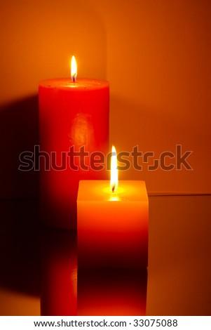 Two candles on orange background - stock photo