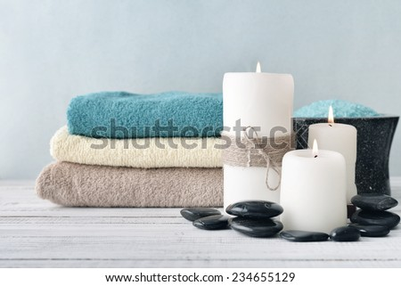 Two candles with lavender flowers and towels on light blue background - stock photo