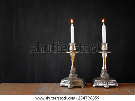 Two candlesticks with burning candles over wooden table and blackboard background - stock photo