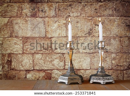 two candlesticks with burning candles over wooden table and old jerusalem stone wall background - stock photo