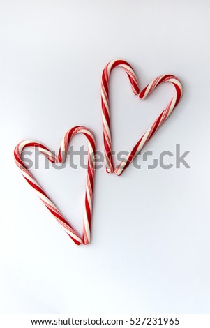 Two candy canes hearts on white background