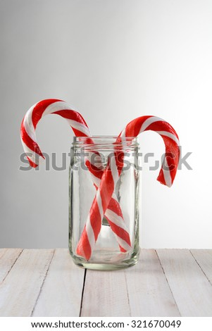 Two Candy Canes in a mason jar. The jar is on a rustic white wood table with a light to dark gray background. - stock photo