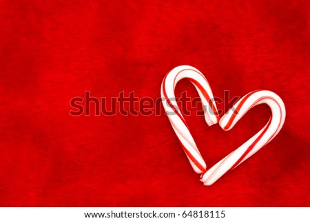 Two candy canes making a heart on a red textured background, Candy cane heart - stock photo