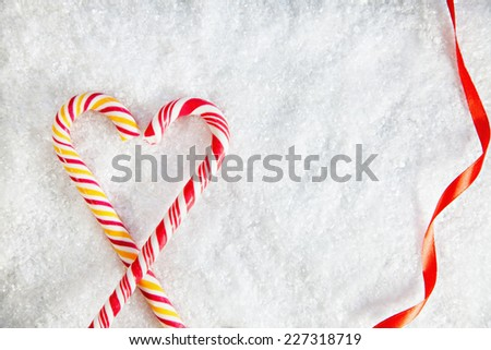 Two Candy Canes Making Heart Shape On Snowy Background. Copy Space - stock photo