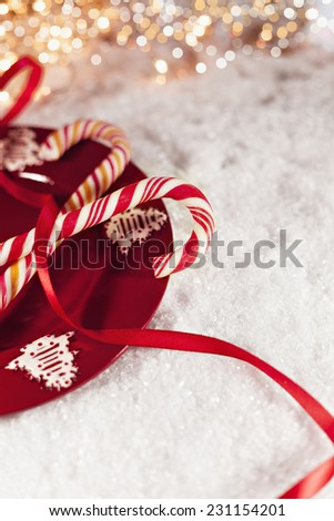 Two Candy Canes On Red Plate With Christmas Decoration Around - stock photo