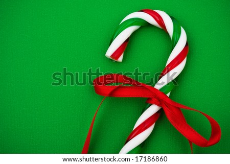 Two candy canes with red ribbon on green background, Christmas background - stock photo