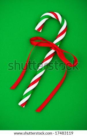 Two candy canes with red ribbon on green background, Christmas background