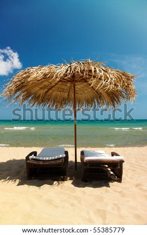 Two canvas chairs and umbrella on beautiful tropical beach - stock photo