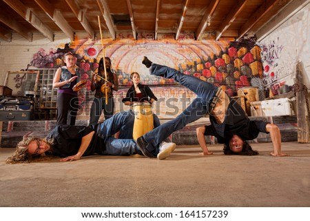 Two capoeira practitioners duel in urban building - stock photo