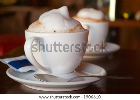 Two cappuccino cups with milk foam and cinnamon - stock photo