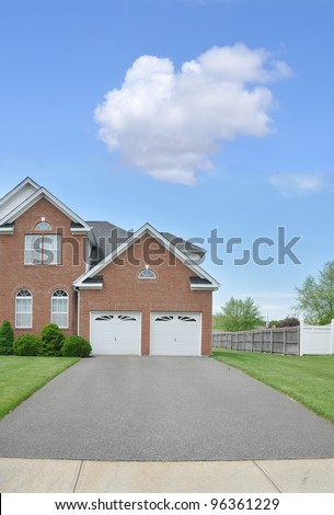 Two Car Garage Blacktop Driveway Suburban Brick Home Beautiful Blue Sky in Residential Neighborhood - stock photo