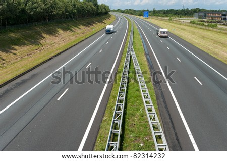 two caravans on an almost empty highway in vacation time - stock photo