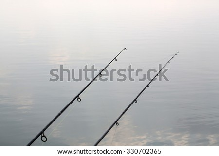 Two carbon fishing rods on background of smooth surface of water tranquility relaxation calm nature outdoor on natural background, horizontal picture - stock photo