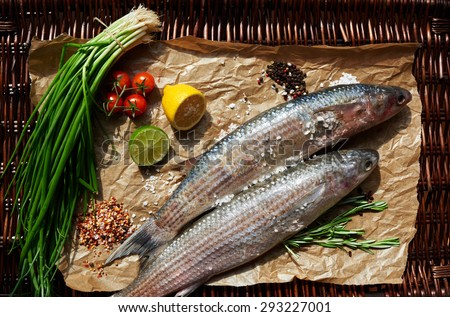 Two carcasses of fresh sea bass chef put on paper to stuff with them with lemon, onion and tomatoes - stock photo