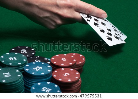 two cards of the player's hand at the game table with chips