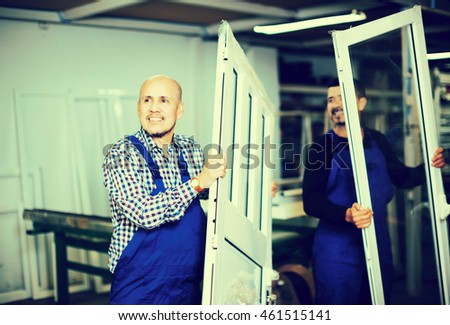 Two careful workers inspecting PVC manufacturing output in workshop