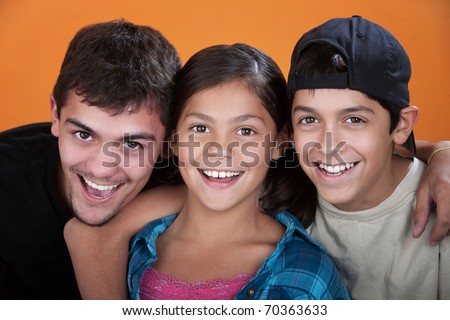 Two caring brothers with sister smiling on orange background - stock photo