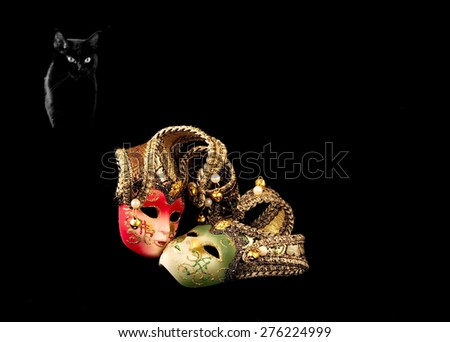 Two carnival mask and a black cat on a black background - stock photo