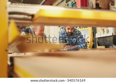 Two carpenters seen through machinery while working - stock photo
