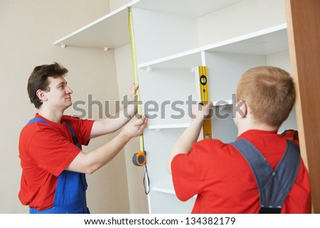 Two carpenters workers joint and settle home built-in cupboard - stock photo