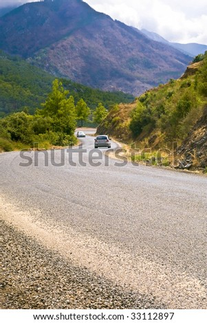 Two cars go up the serpentine road in mountains in cloudy weather