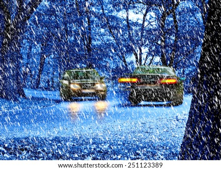 two cars moving in the snow fall by night - stock photo