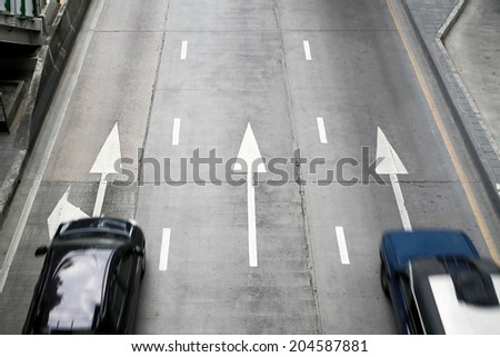 Two cars on street with arrow direction. - stock photo