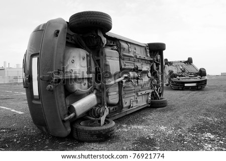 two cars turned upside-down after road collision - stock photo
