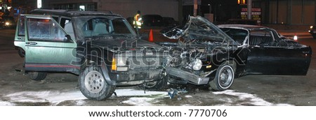 Two cars which were involved in a collision rest at an intersection.