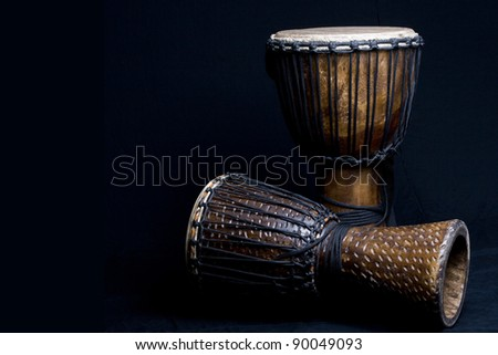 Two carved African djembe drums on dark background. - stock photo