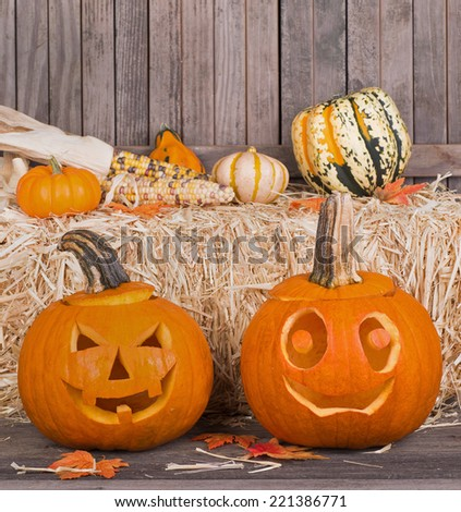 Two carved pumpkins with a hay bale and gourds and corn in background - stock photo