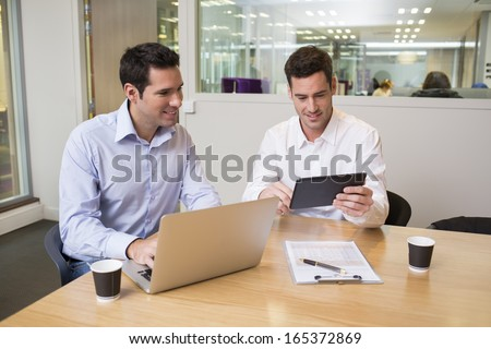 Two casual businessmen working together in modern office with laptop and tablet pc - stock photo