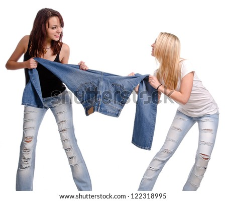 Two casual young women fighting and having a tug of war over a pair of denim jeans, studio portrait isolated on white - stock photo