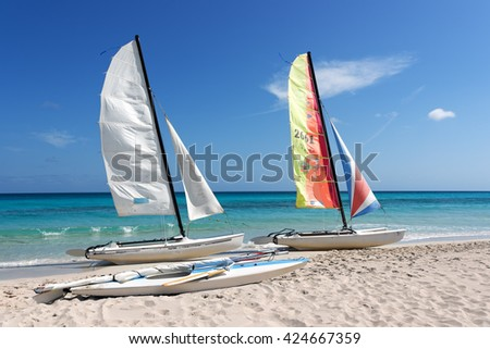 Two catamarans and a sail boat on tropical beach with blue sky and water background - stock photo