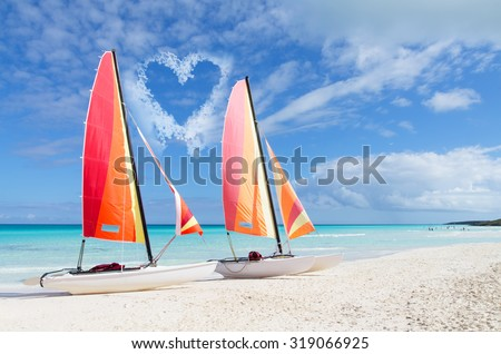 Two catamarans with its colorful sails wide open against blue sky with heart shape clouds, love concept - stock photo