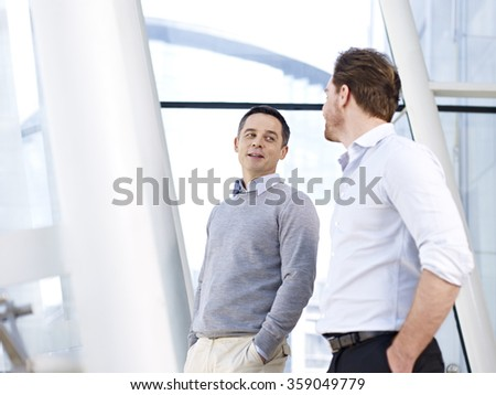 two caucasian business people having a casual conversation in modern office building. - stock photo