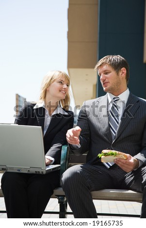 Two caucasian business people having a discussion outdoor - stock photo