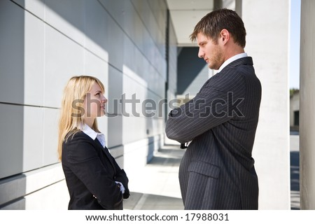 Two caucasian business people looking at each other angrily