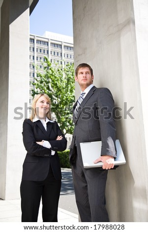 Two caucasian business people standing outside their office