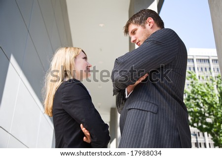 Two caucasian business people staring at each other angrily