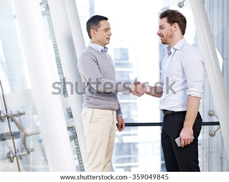 two caucasian business persons shaking hands in modern office building. - stock photo